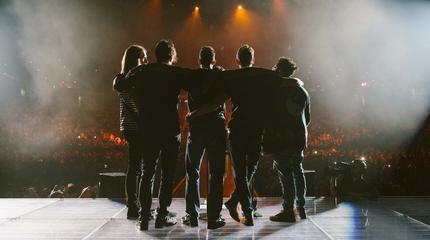Foto de Maroon 5 saludando al público en un concierto desde el escenario