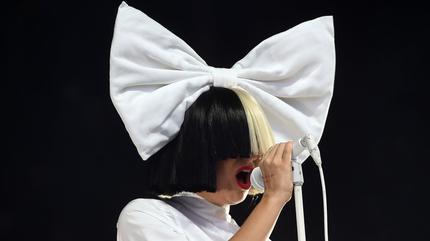 Foto de Sia con el pelo blanco y negro y el lazo gigante