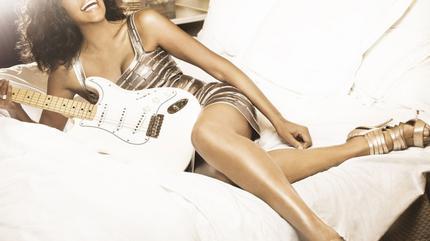 Foto de Whitney Houston posando con una guitarra en una cama